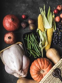 Shopping del ringraziamento con pollame crudo, verdure e frutta. s