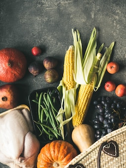 Shopping del ringraziamento con pollame crudo, verdure e frutta.