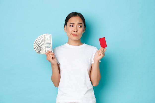 Shopping, denaro e concetto di finanza. una ragazza asiatica attraente indecisa e confusa non può decidere cosa è meglio, carta di credito o contanti, guardando perplesso, pensieroso sul muro blu