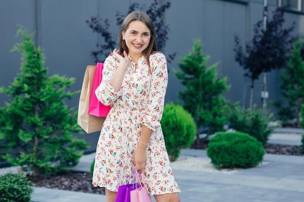 Shopping donna che tiene i sacchetti della spesa guardando la telecamera. bello giovane cliente caucasico che sorride felice.
