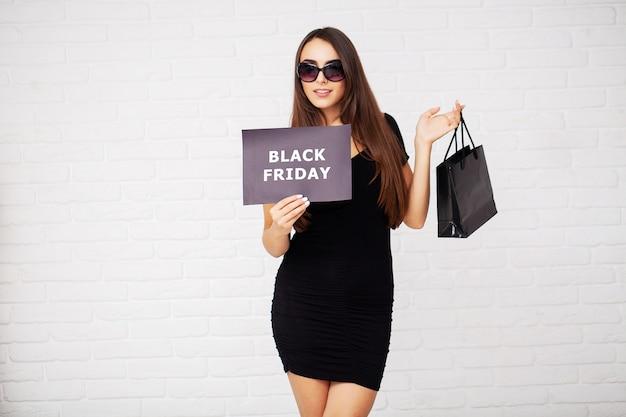 Shopping. donne che tengono gli spazii in bianco di sconto nelle vendite di venerdì nero