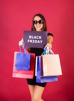 Shopping. donne che tengono le borse colorate su rosso nella festa nera di venerdì