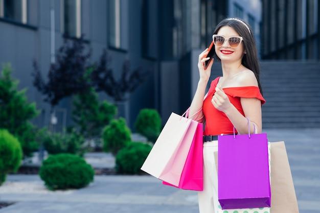 Shopping e concetto di turismo. bella ragazza con le borse della spesa. maniaco dello shopping. vendita e sconto. ragazza shopping online.