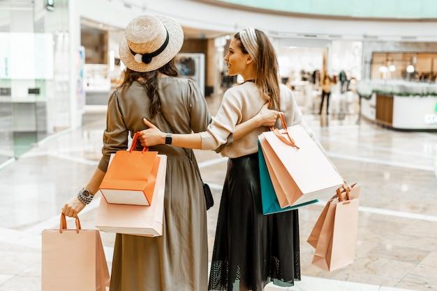 Shopping e divertimento, centro commerciale all'interno. due belle ragazze con sacchi di carta al centro commerciale. la gioia del consumo, lo shopping regalo, le vacanze.