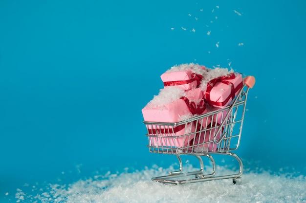 Shopping natalizio in loco. cerca regali di natale per tutta la famiglia, concetto. il carrello è pieno di scatole regalo