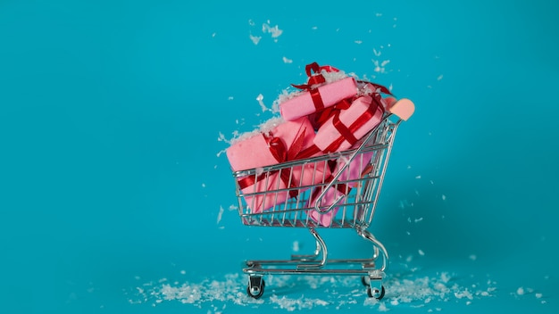 Shopping natalizio. l'acquisto di regali per il nuovo anno, il concetto. il carrello è pieno di scatole regalo