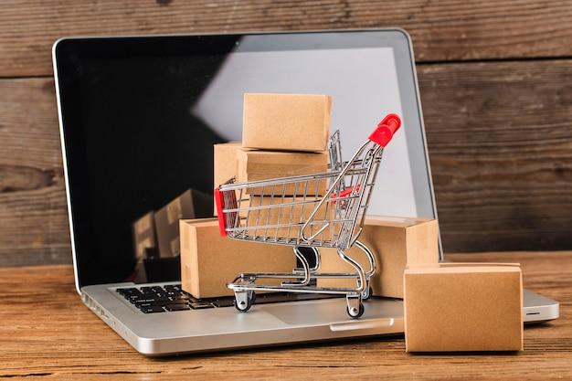 Shopping online a casa conceptcartoni in un carrello sulla tastiera di un computer portatile