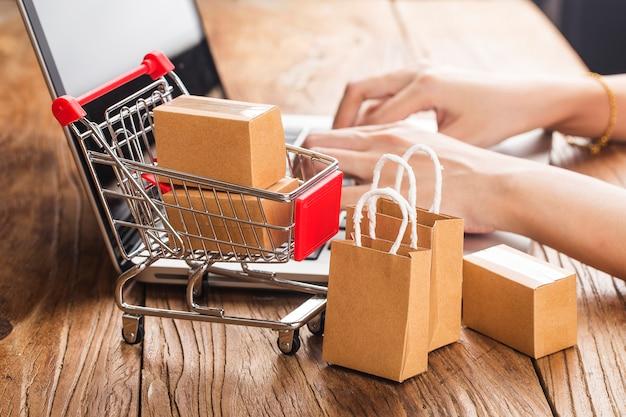 Shopping online a casa concetto. scatole in un carrello sulla tastiera di un computer portatile.