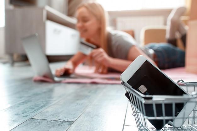 Shopping online a casa. la carta di credito e lo smartphone sono pronti per la vendita di un giorno su un acquirente con laptop