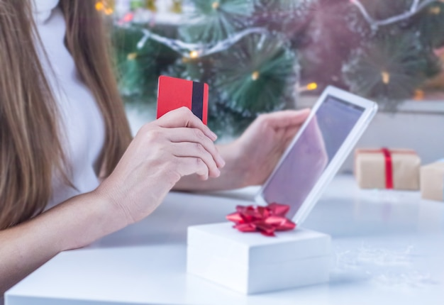 Shopping online di natale. la donna vaga in maglione bianco sta acquistando i regali di natale con il computer portatile e in possesso di una carta di credito