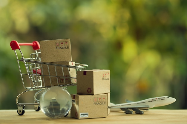 Shopping online e concetto di e-commerce: scatole di carta in un carrello e un globo di cristallo, piano.