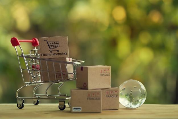 Shopping online e concetto di e-commerce: scatole di carta nel carrello e globo di cristallo.
