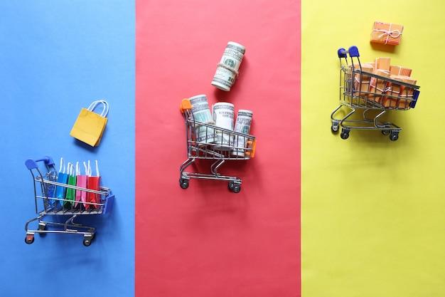 Shopping online, shopping bag di carta e banconote, scatola pacchi marrone sul carrello in miniatura modello su sfondo colorato