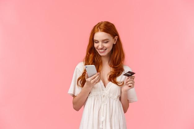 Shopping, pagamento facile e concetto di persone. ragazza bella rossa in abito bianco raccolta presente nel negozio online, in possesso di smartphone e carta di credito, pagando via internet per la consegna
