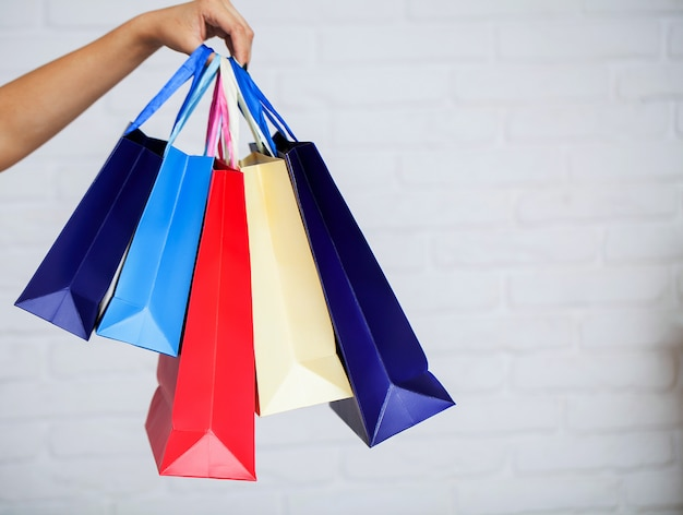 Shopping. primo piano del sacchetto della spesa della carta di colore della tenuta della donna sul fondo bianco della parete