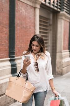 Shopping ragazza guardando il suo telefono cellulare
