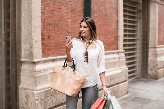 Shopping ragazza usando il suo telefono cellulare