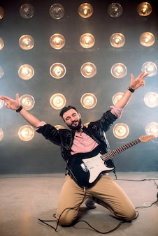 Showman maschio con chitarra elettrica sul palco con decorazioni di luci.