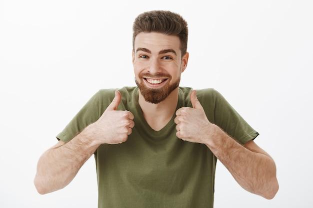 Sì al cento per cento. ritratto del ragazzo caucasico barbuto attraente ottimista felice eccitato in maglietta che solleva i pollici in su in approvazione e come gesto che è allegro e solidale accettando una buona idea