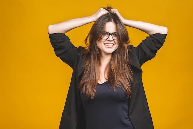 Sì! donna abbastanza estremamente felice di affari che celebra il suo successo isolato contro la parete gialla.