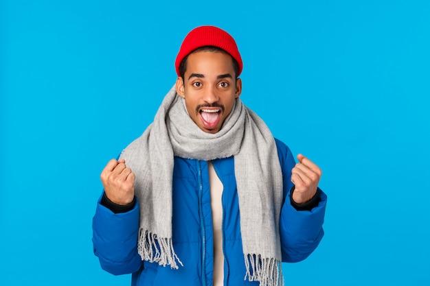 Sì, possiamo farlo. incoraggiato e motivato bell'uomo afroamericano allegro in giacca imbottita, berretto invernale sciarpa, braccia serrate che trionfano, si prepara, aumenta la fiducia