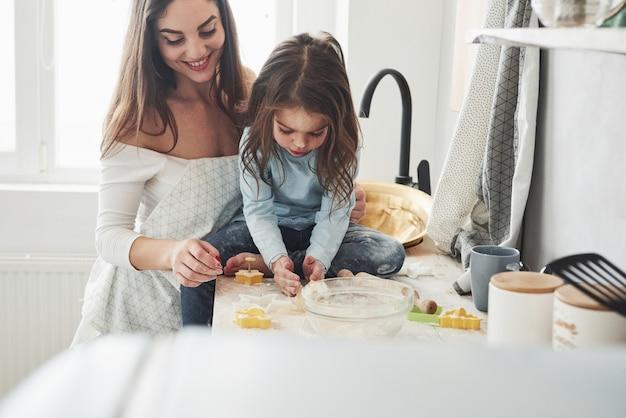 Si sedette sul tavolo. la figlia e la mamma felici stanno preparando insieme i prodotti da forno. piccolo aiutante in cucina