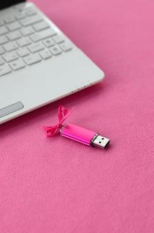 Si trova una brillante scheda di memoria flash usb rosa con un fiocco rosa