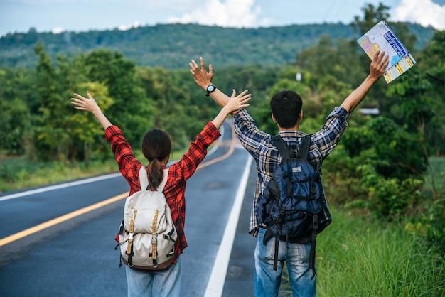 Sia i turisti maschi che femmine portano uno zaino, si fermano sulla strada e alzano le mani su entrambi i lati.