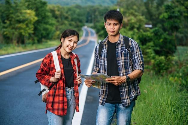 Sia i turisti maschili che quelli femminili stanno a vedere la mappa sulla strada.