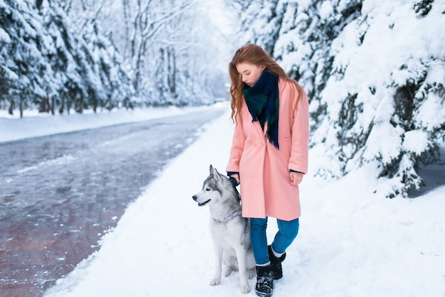 Siberian husky seduto vicino alla giovane donna