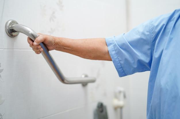 Sicurezza paziente asiatica della maniglia del bagno della toilette di uso della donna senior in ospedale.
