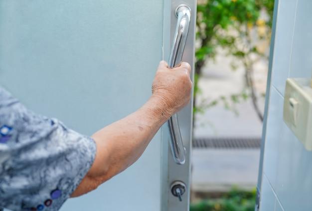 Sicurezza senior o anziana asiatica della maniglia del bagno della toilette di uso della donna della signora anziana.