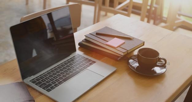 Sideview del desktop dell'ufficio con il computer portatile in bianco e vari strumenti dell'ufficio sullo scrittorio di legno.