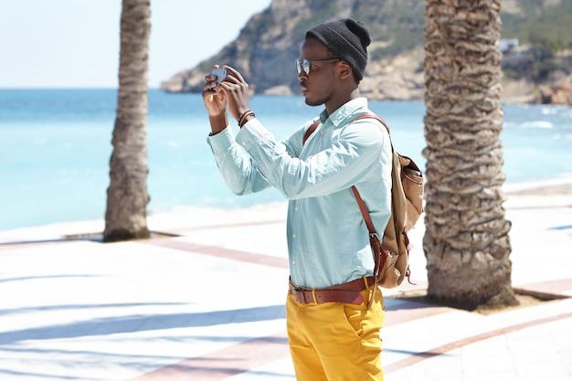 Sideview di giovane viaggiatore nero alla moda in vacanza con lo smartphone con entrambe le mani mentre fotografa o registra video di bellezza intorno a lui per pubblicarli sui suoi account sui social media