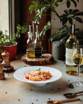 Sideview di pasta con salsa di pomodoro e parmigiano in ciotola bianca