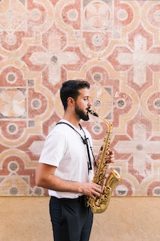 Sideways man medium shot a suonare il sassofono con sfondo geometrico