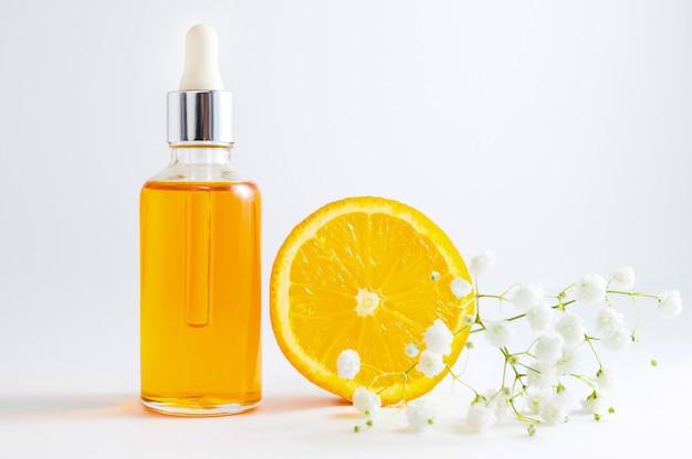 Siero di vitamina c in flacone cosmetico con contagocce. cosmetici spa biologici con ingredienti a base di erbe.