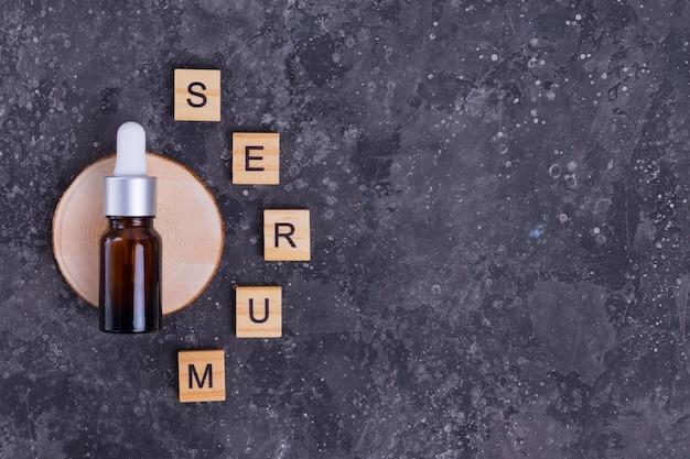 Siero idratante con collagene e mucina di una lumaca per la pelle del viso contro rughe e acne in una bottiglia di vetro marrone con lettere di siero su uno sfondo grigio