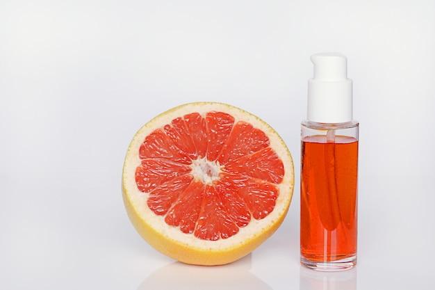Siero per il viso con estratto di pompelmo. siero di agrumi all'arancia con olio essenziale di pompelmo e pompelmo in una sezione cosmetici biologici con estratto di agrumi