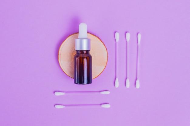 Siero viso idratante in una bottiglia di vetro per il viso con lumache di collagene e mucina per la pelle del viso contro rughe e acne con bastoncini per il trucco su uno sfondo viola