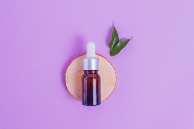 Siero viso idratante in una bottiglia di vetro per il viso con lumache di collagene e mucina per la pelle del viso contro rughe e acne con foglie verdi di un albero su uno sfondo viola