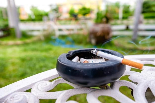 Sigaretta che brucia con fumo sul posacenere in ceramica