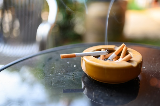 Sigaretta che brucia con il fumo sul posacenere
