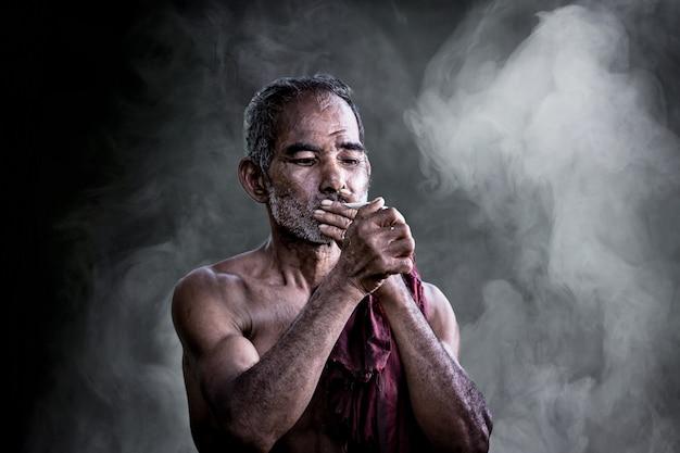 Sigaretta di fumo del vecchio asiatico e il fumo rilasciato dalla bocca contro oscurità