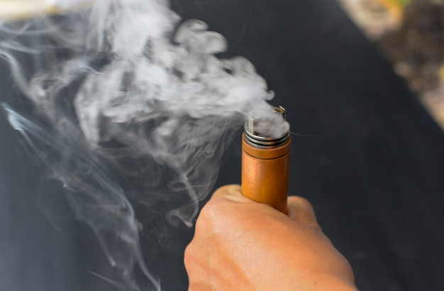 Sigaretta elettrica che brucia in mano con fumo bianco, sigaretta elettronica, varpo.
