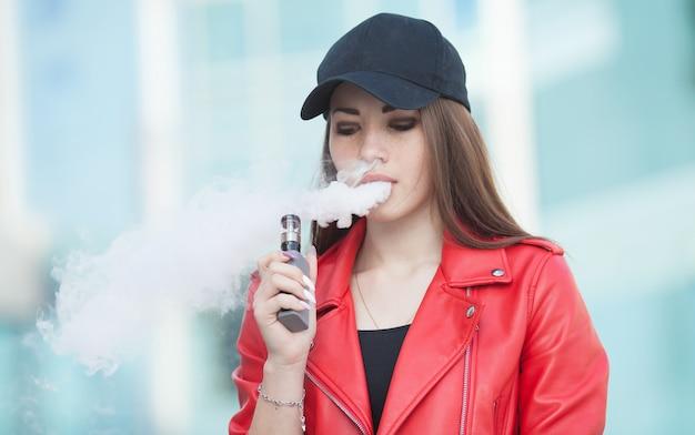 Sigaretta elettronica di fumo della giovane bella donna (vaping) con fumo