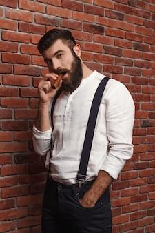Sigaro di fumo brutale del giovane uomo bello sul muro di mattoni.