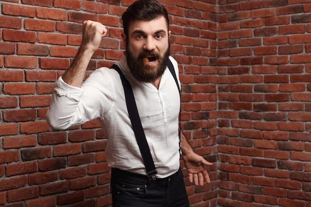 Sigaro di fumo del giovane uomo bello brutale di rabbia sul muro di mattoni.