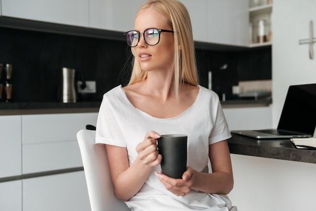 Signora abbastanza pensierosa con la tazza di tè che si siede nella cucina