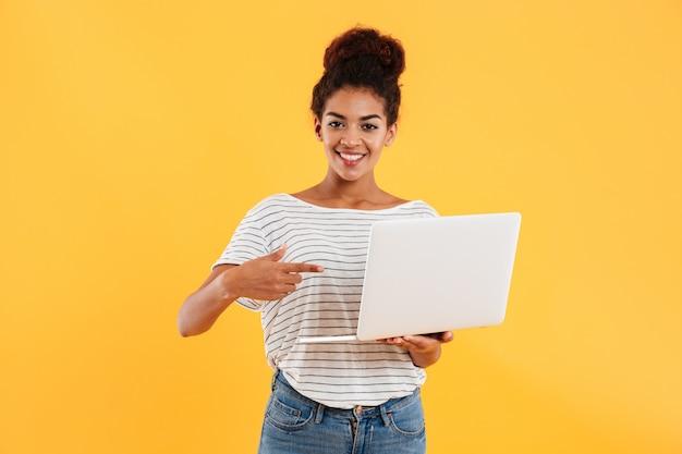 Signora africana abbastanza allegra e computer portatile giudicante isolati